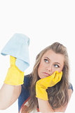 Bored young maid in yellow gloves using duster