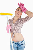 Tired young woman holding broom