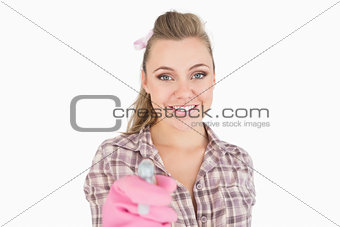 Portrait of smiling young woman holding spray bottle