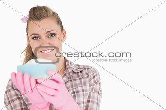 Portrait of smiling woman holding sponge