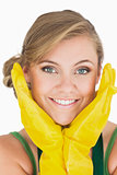 Closeup of smiling young maid with yellow gloves