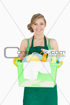 Portrait of young maid carrying cleaning supplies