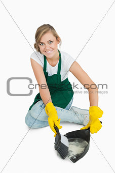 Portrait of smiling maid using brush and dust pan