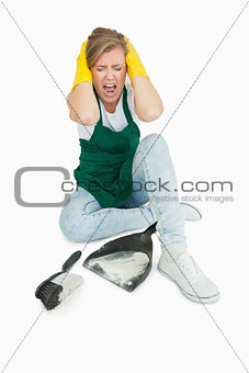 Tired maid screaming as she sits with brush and dust pan