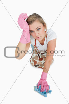 Portrait of tired young woman cleaning floor