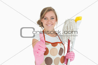 Portrait of maid with cleaning supplies gesturing thumbs up sign