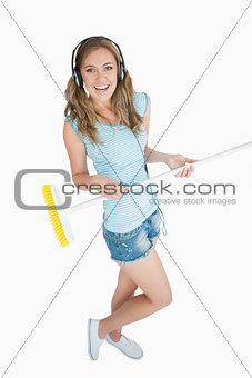 Young woman with broom enjoying music over headphones