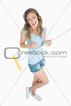 Woman playing air guitar with broom while listening music over headphones