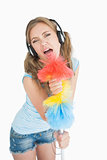 Woman holding feather duster as microphone and listening music over headphones