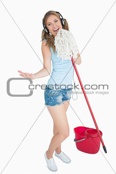 Woman holding broom as microphone and listening music over headphones