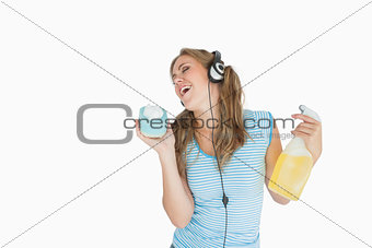 Woman with sponge and spray bottle enjoying music over headphones