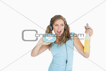 Young woman with sponge and spray bottle enjoying music over headphones