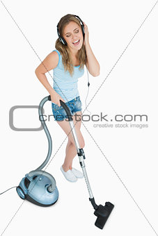 Woman enjoying music over headphones while vacuuming