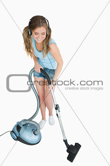 Woman listening music over headphones while vacuuming
