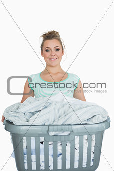 Portrait of smiling woman carrying laundry basket