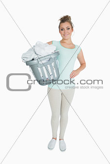 Portrait of young woman carrying laundry basket