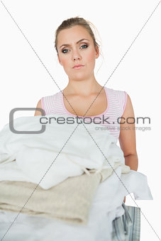 Portrait of woman carrying stack of clothes