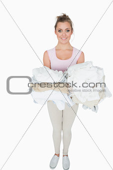 Portrait of smiling woman carrying stack of clothes
