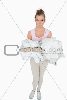 Portrait of young woman carrying stack of clothes