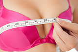 Woman measuring chest in pink bra