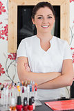 Confident woman with arms crossed at reception in nail salon