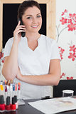 Woman answering phone at reception of nail salon