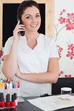 Woman answering phone at reception of nail salon