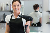 Female hairdresser holding hair dryer