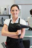 Confident female hairdresser holding hair dryer