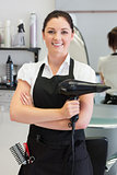Confident female hairdresser holding hair dryer