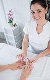 Portrait of manicurist filing womans nails