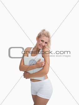 Portrait of young happy woman hugging weighing scales