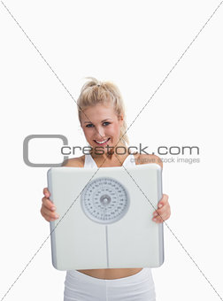 Portrait of young happy woman holding out weighing scales