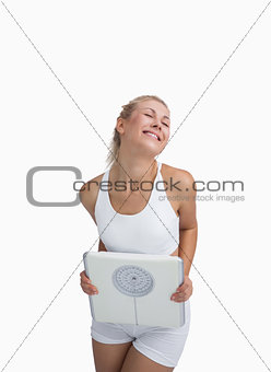 Excited young happy woman holding weighing scales
