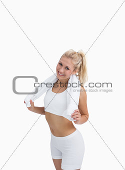 Happy woman in sportswear holding towel around neck