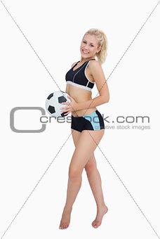 Portrait of happy woman in sportswear holding football