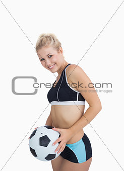 Portrait of happy woman in sportswear with football