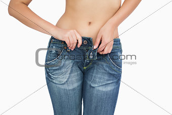 Midsection of slim woman buttoning jeans