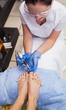 Nail technician removing callus at feet