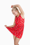 Young woman in red summer dress dancing