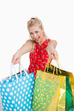 Cute excited young woman holding out shopping bags