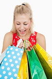 Cute excited woman looking into her shopping bags
