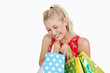 Cute excited young woman with shopping bags
