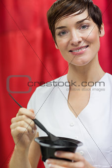 Portrait of woman mixing hair color over red backdrop
