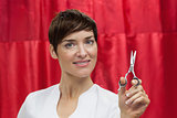 Portrait of confident female hairdresser with hair scissors