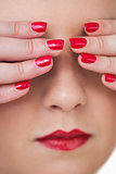 Macro shot of young woman covering eyes with red painted finger nails