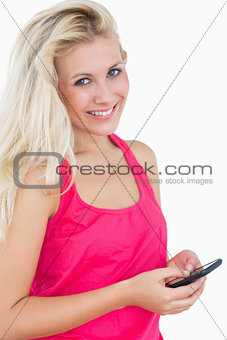 Portrait of happy casual young woman using smartphone
