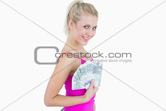 Portrait of happy young woman holding fanned euro banknotes