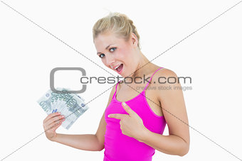 Portrait of happy woman pointing at fanned euro banknotes