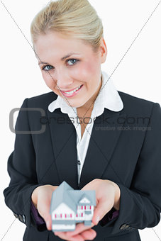 Portrait of business woman holding model house